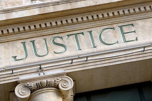 "An exterior of a law building with the word ""justice"" enscribed on it"