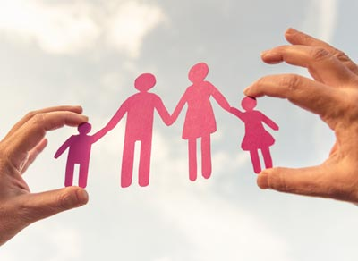 A hand holds a paper cutout of a family holding hands